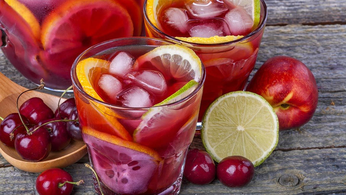 Sangria bottle and glasses with lemon and cherries.